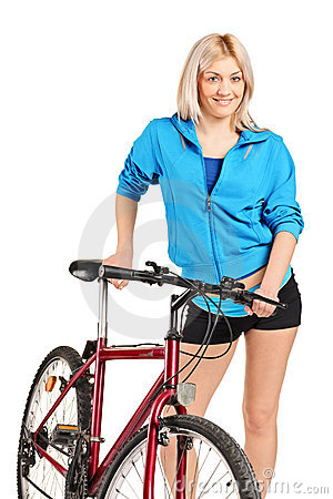 Smiling blond female posing next to a bicycle