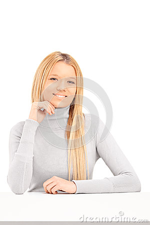 A smiling blond female posing on a table