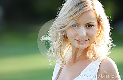 Smiling blonde girl. Portrait of happy cheerful beautiful young woman, outdoors. Stock Photo