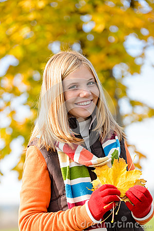 Smiling blonde teen girl autumn forest leaves