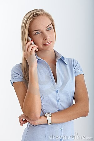 Smiling blonde teen using cellphone