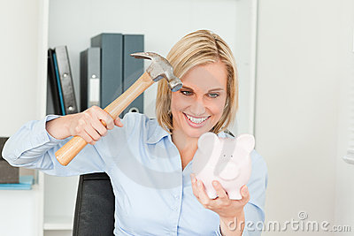 Smiling blonde woman destroying her piggy bank