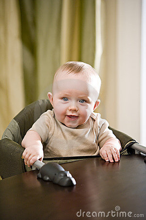 Smiling blue-eyed baby in highchair