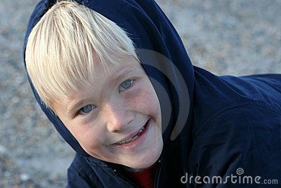 Smiling Boy Bundled up in Clothing at the Beach