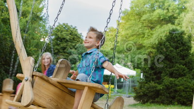 Smiling boy and girl having fun at playground. Children playing outdoors in summer. Teenagers riding on a swing outside.  stock footage