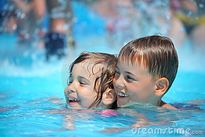 Smiling boy and girl swimming in pool in aquapark