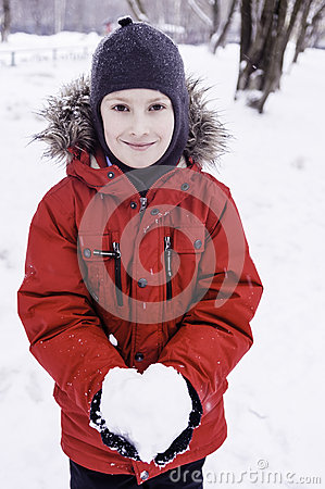 Smiling boy holding snow heart