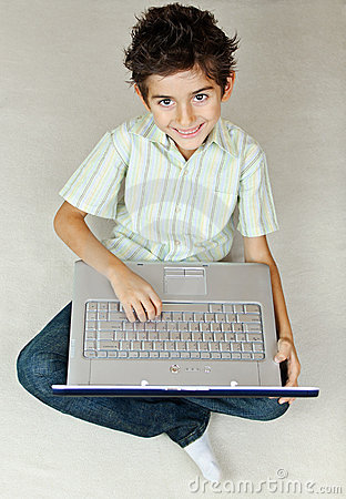 Smiling boy with laptop working on the floor