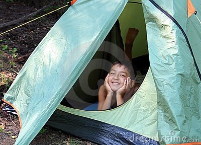Smiling boy looking from tent