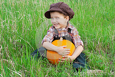 Smiling boy with pumpkin on the grass