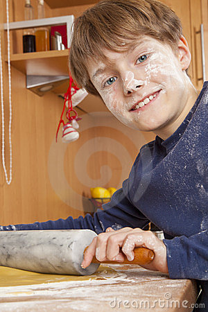 Smiling boy rolling dough