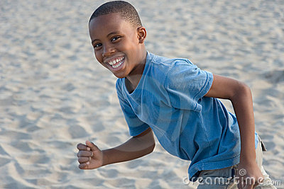 smiling boy running with sand
