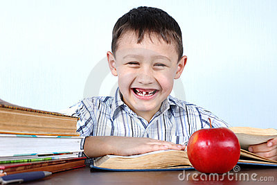 Smiling boy without several tooth with apple