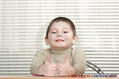 Smiling boy showing both thumbs up