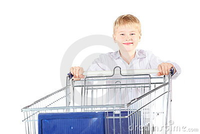 Smiling boy is standing near shoping basket
