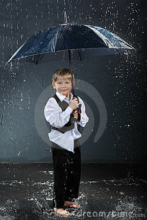 Smiling boy standing under umbrella in rain