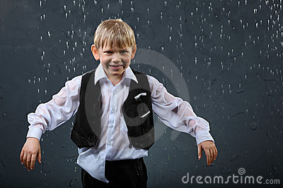 Smiling boy stands in rain