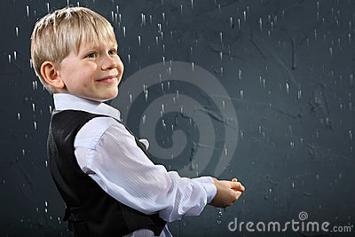 Smiling boy stands in rain and catches drops