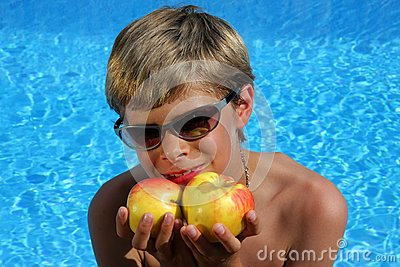 Smiling boy with sun glasses presenting apples