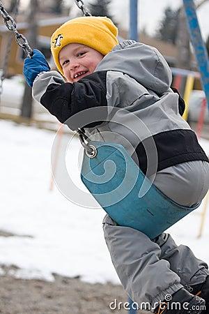 Smiling boy swinging