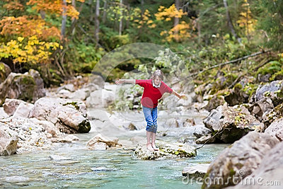 Smiling boy trying to cross wild mountain river