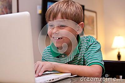 Smiling boy using white laptop