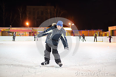 Smiling boy wearing in black suit and blue hat skates