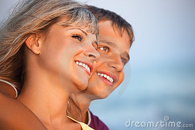 Smiling boy and young woman on beach in evening