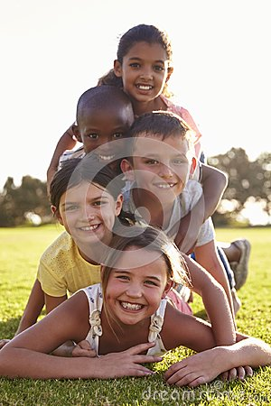 Free Smiling Boys And Girls Lying In A Pile On Grass In Summer Stock Images - 99965514