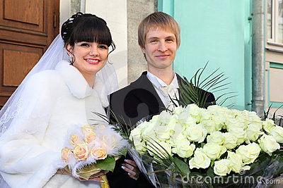 Smiling bride and groom with bouquets