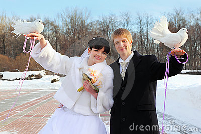 Smiling bride and groom hold white doves