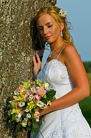 Smiling bride leaning on tree