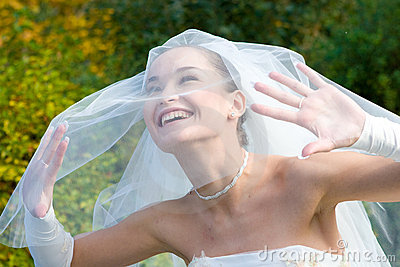 A smiling bride looks through the veil