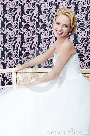 Smiling bride put out her toungue sitting bench