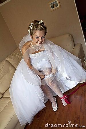 Smiling bride setting the garter