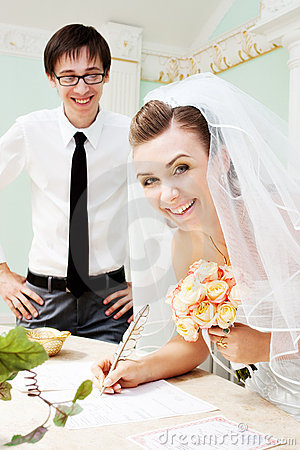 Smiling bride signing marriage papers