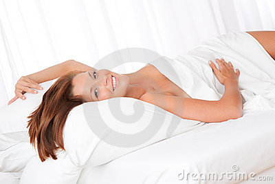 Smiling  brown hair woman lying in white bed