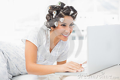 Smiling brunette in hair rollers lying on her bed using her laptop