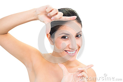 Smiling brunette looking at camera framing her face with hands