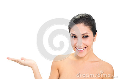 Smiling brunette presenting with hand looking at camera
