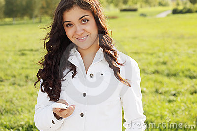 Smiling brunette with white cellphone