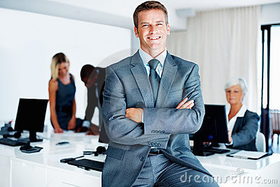 Smiling business man with colleagues in background