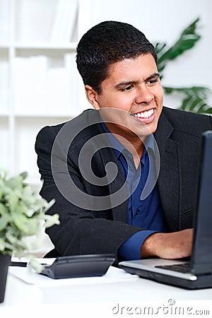 Smiling business man executive using a computer