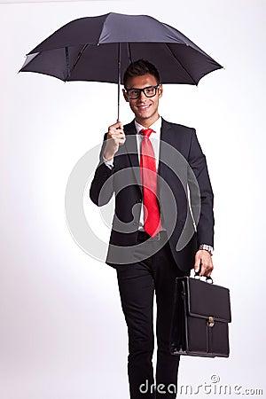 Smiling business man under an umbrella walking