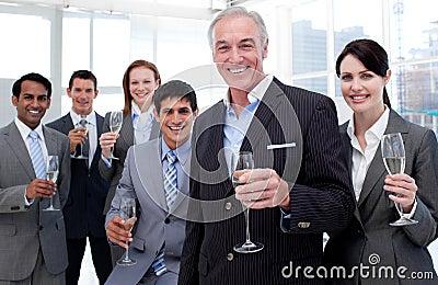 Smiling business team holding glasses of Chamoagne