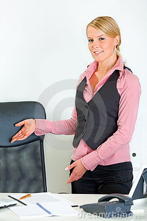 Free Smiling Business Woman Inviting To Sit On Chair Stock Images - 19711044