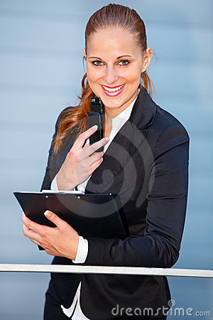 Smiling business woman with mobile and clipboard