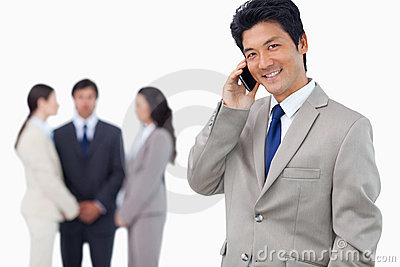 Smiling businessman on cellphone and team behind him