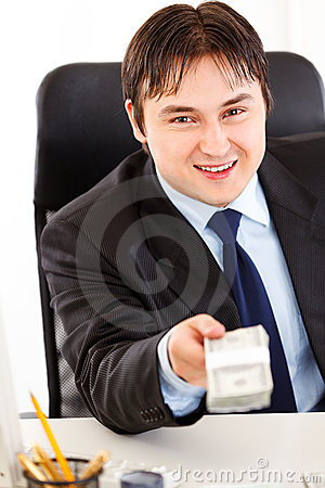 Smiling businessman giving dollar pack