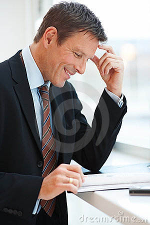 Smiling businessman going through documents